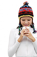Young woman wearing winter hat and staring down at mug of hot chocolate - Asia Images Group