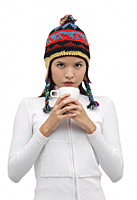 Young woman wearing winter hat and holding mug of hot chocolate - Asia Images Group