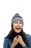 Young woman wearing winter hat and scarf, smiling and looking up - Asia Images Group