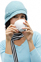 Young woman wearing wool hat and scarf, drinking hot chocolate - Asia Images Group