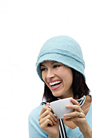 Young woman wearing wool hat and scarf, holding mug and laughing - Asia Images Group