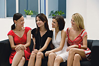 Four young women wearing dresses and sitting on couch - Asia Images Group