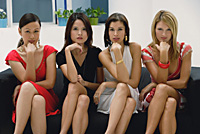 Four young women wearing dresses, legs crossed and looking at camera, sitting on couch - Asia Images Group