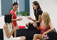 Four women sitting on couch holding drinks and talking - Asia Images Group