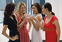 Four women standing and toasting glasses, smiling - Asia Images Group