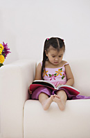 A young girl sitting on the couch with a book - Asia Images Group