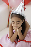 A young girl at a party with balloons - Asia Images Group