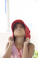 A young girl with a red hat - Asia Images Group