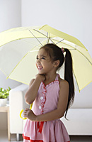 A young girl with an umbrella - Asia Images Group