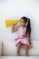 A young girl plays with a yellow cone - Asia Images Group