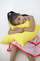 A young girl hugs a cushion - Asia Images Group
