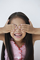 A young girl covers her eyes with her hands - Asia Images Group