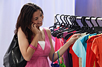 A teenage girl out shopping while she talks on her cellphone - Asia Images Group