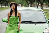 A young woman in a green dress with a green car - Asia Images Group