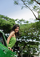 A young woman leans out of the window of a car - Asia Images Group