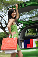 A young woman puts her shopping in the back of a car - Asia Images Group