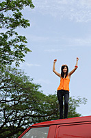 A young woman dances on the top of a red van - Asia Images Group