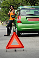 A woman talks on her cellphone while leaning on a car - Asia Images Group