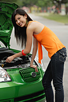 A young woman looks under the hood of a car - Asia Images Group