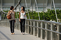 Two friends walk across a bridge together - Asia Images Group
