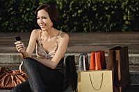 A woman with lots of shopping bags uses her cellphone - Asia Images Group