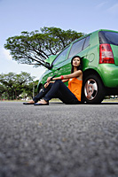 A young woman sits on the ground leaning against a car - Asia Images Group
