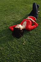 A woman relaxes on grass - Asia Images Group