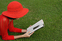 A woman reads while lying on grass - Asia Images Group