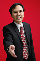 A businessman extends his hand to shake hands - Asia Images Group