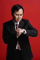 A businessman checks his watch for the time - Asia Images Group