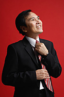A businessman adjusts his tie - Asia Images Group