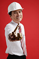 A man wearing a shirt and tie with a hardhat - Asia Images Group