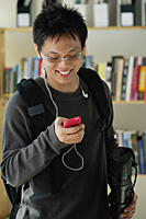 A young man listens to music in the library - Asia Images Group