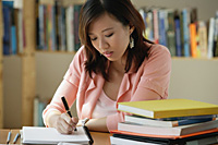 A young woman studies in the library - Asia Images Group