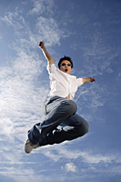 A young man jumps for joy - Asia Images Group