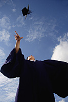 A recent graduate throws his hat in the air in celebration - Asia Images Group