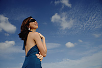 A young woman with sunglasses stands with the sky in the background - Asia Images Group