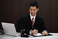 A businessman in a suit sits at his desk - Asia Images Group