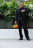 A man checks his watch while he holds a bunch of flowers - Asia Images Group