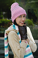 A woman tries to keep warm in a hat and gloves as she smiles at the camera - Asia Images Group