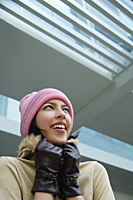 A woman tries to keep warm in a hat and gloves - Asia Images Group