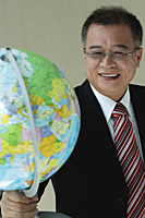 A man in suit holds a globe - Asia Images Group