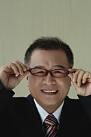 A man smiles at the camera as he puts on his glasses - Asia Images Group
