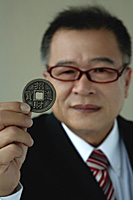 A man holds out a Chinese coin - Asia Images Group