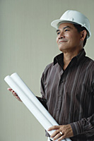A man with a helmet and rolled up plans - Asia Images Group