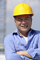 A man with a yellow helmet smiles at the camera - Asia Images Group
