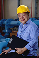 A man with a yellow helmet smiles at the camera as he works indoor - Asia Images Group