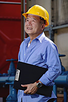 A man with a yellow helmet at work indoor - Asia Images Group