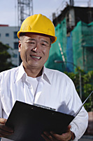 A man with a yellow helmet smiles at the camera, holding file - Asia Images Group