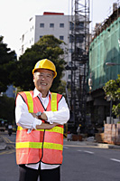A man with a yellow helmet smiles at the camera, hands crossed - Asia Images Group